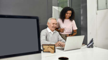 Aged man, senior intern looking at laptop while showing results to his young colleague, Friendly female worker mentoring and training new employee, monitoring his progress at work 免版税图像 - 157325054