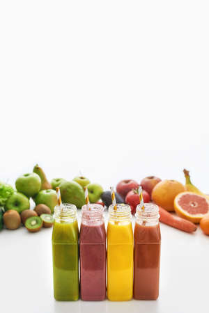 Composition of healthy detox juices and smoothies in bottles with paper straws, Various colorful fruits and vegetables isolated over white background 免版税图像 - 157325055