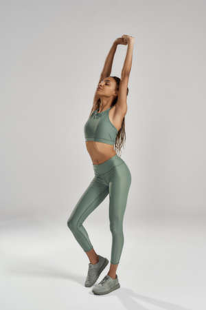Full length shot of a young athletic slim mixed race fitness woman in sportswear stretching her arms, warming up while standing isolated over grey background 免版税图像 - 157325073