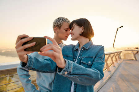 Lesbian couple standing on the bridge, posing while taking a selfie picture, watching the sunrise together 免版税图像 - 157325076