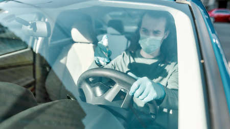 Man wearing medical mask and protective gloves spraying antibacterial disinfectant spray on steering wheel while cleansing car interior to prevent virus