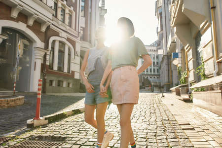 Young lesbian couple, two women in casual wear holding hands, walking along the street while exploring the city on a sunny day 免版税图像 - 157325081