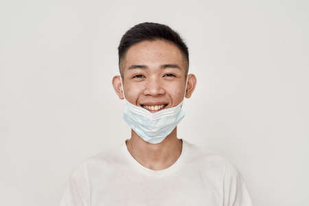 Portrait of young asian man smiling at camera while having medical mask on his chin isolated over white background. Health care, prevention, safety concept 免版税图像 - 157325085