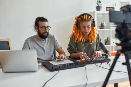 Woman with dreadlocks singing and playing. Female and male blogger making music using synthesizer, drum pad machine and laptop, recording video blog or vlog at home 免版税图像 - 157325088