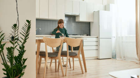 A little girl stirring her quick breakfast standing on a stoll on her knees in a big bright kitchen 免版税图像 - 157325090