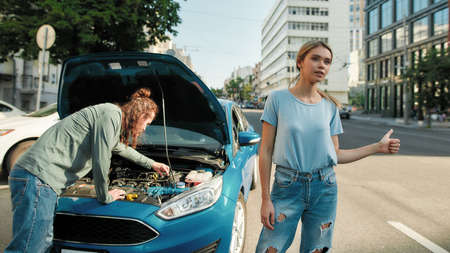 Couple got trouble on the road, Attractive young woman showing hitchhiking gesture, asking for help while man examining broken down car, trying to fix it 免版税图像
