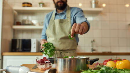 Cropped shot of man, chef cook adding basil leaf to the pot with chopped vegetables while preparing healthy meal, soup in the kitchen. Cooking at home, Italian cuisine concept