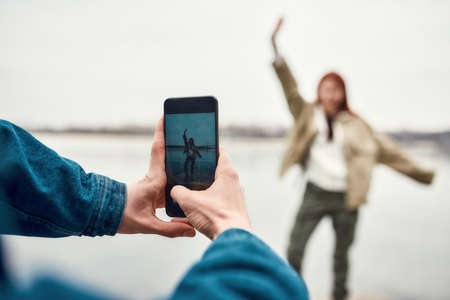 Close up of hands of young guy holding smartphone while taking photo of his girlfriend outdoors 免版税图像