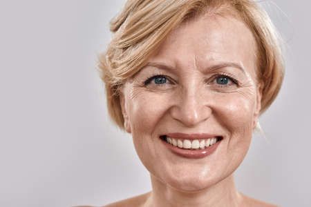 Close up shot of face of beautiful middle aged woman smiling at camera while posing isolated against grey background 免版税图像 - 157325113