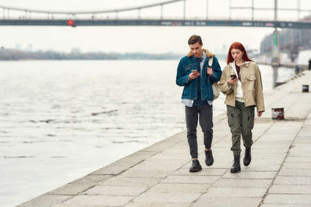 Full length shot of two teenagers totally absorbed in their smartphones, ignoring each other while walking along the riverside together 免版税图像 - 157325114