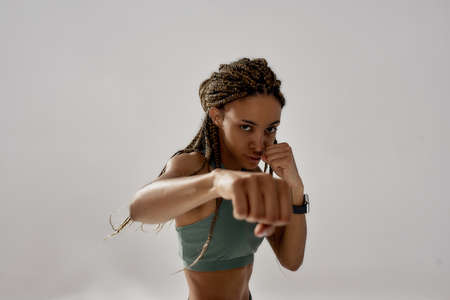 Practicing boxing. Young muscular beautiful mixed race woman, female boxer looking at camera and punching while standing isolated over grey background