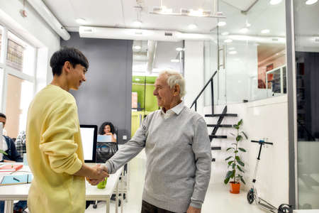 Cheerful aged man, senior intern shaking hands with young male colleague at his new job in the modern office 免版税图像 - 157325118