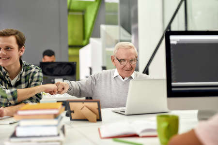 Aged man, senior intern looking at the screen of his laptop and doing a fist bump with his young colleague, Friendly male worker engaging new employee while working in the office
