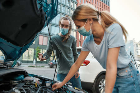 Man in medical mask helping girl with her auto while she is examining, looking at her broken car with open hood, standing on the city street 免版税图像 - 157325122
