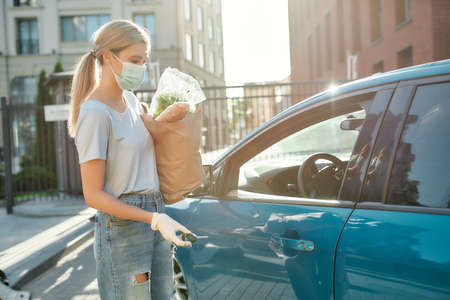 Young woman in medical mask and protective gloves standing with grocery bag near her blue car, holding key while going to open the car door 免版税图像 - 157325123