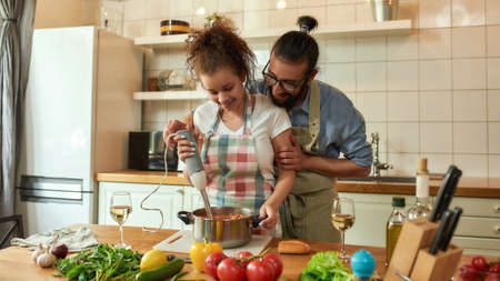 Young couple preparing a meal together in the kitchen. Italian man, chef cook helping his girlfriend to use hand blender. Cooking at home, Italian cuisine