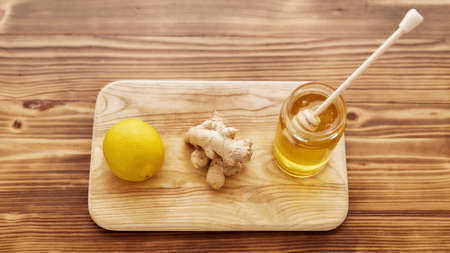Close up of fresh ginger, lemon, honey in a jar with dropper on the wooden board, Preparation of cold and flu remedy cure drink 免版税图像