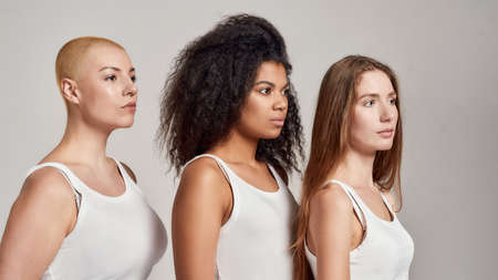Portrait of three confident young diverse women wearing white shirts looking aside while posing together isolated over grey background