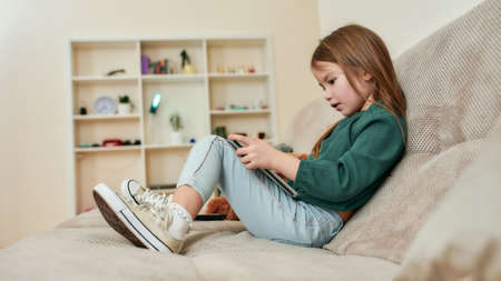 A cute small girl holding tablet sitting on a sofa in front of bookshelves 免版税图像 - 157325129