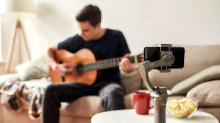 Teenage guy using smartphone while playing guitar and recording video at home. Blogging, technology concept. Focus on mobile phone on a tripod