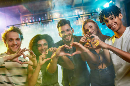 Nightclub time. Young men and women showing heart signs while posing together for camera. Multiracial group of friends hanging out at party in the bar 免版税图像 - 157325131