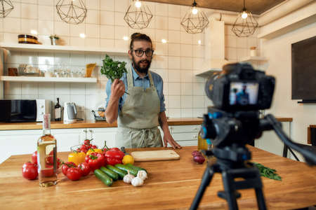 Young man, Italian cook in apron looking at camera, holding basil, filming himself for culinary blog while preparing healthy meal with vegetables in the kitchen 免版税图像 - 157325134
