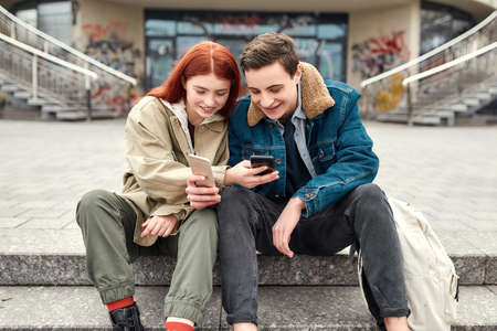 Two teenagers holding smartphones, looking at the screen, discussing something and smiling while sitting on the steps outdoors