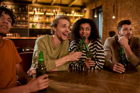 Friends in the bar watching sports match on TV together, drinking beer, clinking bottles and cheering for team. People, leisure, friendship and entertainment concept