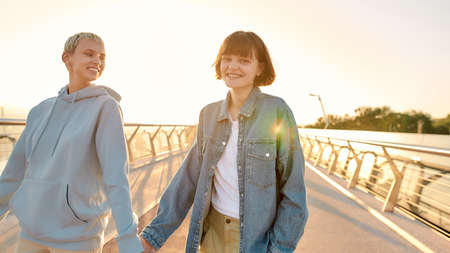 Happy lesbian couple laughing, having fun, holding their hands while walking on the bridge and watching the sunrise together. Homosexuality, LGBT and love concept 免版税图像 - 157507502
