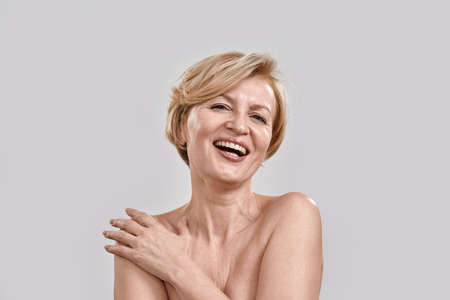 Portrait of beautiful middle aged woman laughing at camera, touching her skin, posing isolated against grey background. Beauty, skincare concept 免版税图像 - 157507505