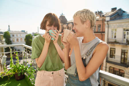 Two cheerful women drinking coffee or tea while standing on the balcony. Young lesbian couple spending their day together 免版税图像 - 157507520