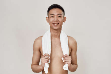 Portrait of shirtless young asian man with problematic skin and hyperpigmentation on his face posing with towel around his neck isolated over white background 免版税图像 - 157507525