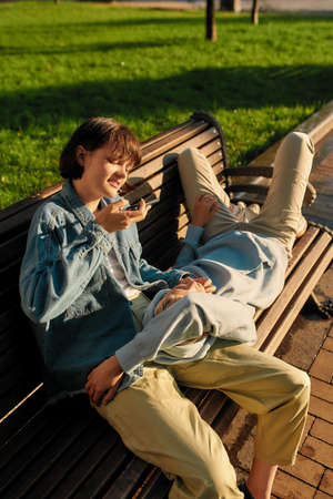 Young woman taking picture of her girlfriend while relaxing on the bench in the city park on a sunny day. Lesbian couple spending time together outdoors 免版税图像