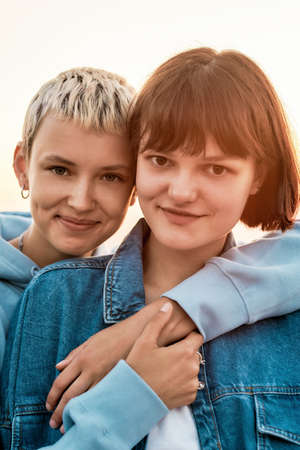 Portrait of two attractive young women with short hair smiling at camera, Young couple spending time together, hugging while posing outdoors
