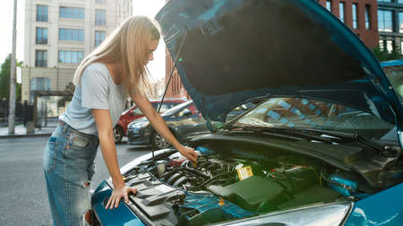 Young woman standing on the city street while examining her broken down car with open hood