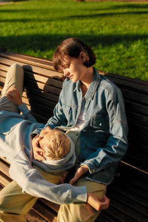 Two young women relaxing on the bench in the city park on a sunny day. Lesbian couple spending time together outdoors 免版税图像 - 157507536
