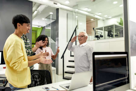 Aged man, senior intern looking cheerful, raising his arms after completing first task at work, Friendly workers applauding, cheering new employee in the office 免版税图像 - 157507541