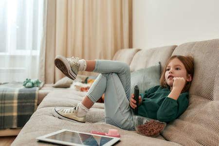 A small cute girl watching TV sitting leg to leg on a sofa holding a TV remote 免版税图像 - 157507544
