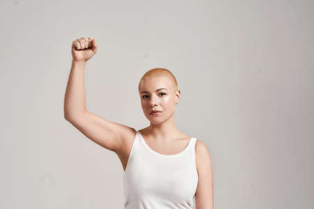 Portrait of attractive young caucasian woman with shaved head wearing white shirt, looking at camera while raising clenched fist, standing isolated over grey background 免版税图像 - 157507549