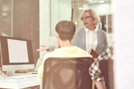 Serious aged woman, female company executive training new employee, monitoring progress and criticising his work while standing in the office 免版税图像 - 157507553