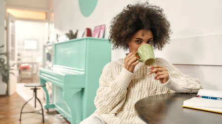 A cute young dark-skinned woman wearing fashionable clothes looking into a camera while drinking coffee and sitting on a chair 免版税图像 - 157507704