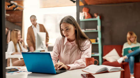 A pretty yound brutette sitting at a table working with a laptop with her female colleagues discussing fashion trends on a background 免版税图像 - 157507706