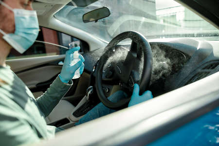 Cropped shot of man wearing medical mask and protective gloves spraying antibacterial disinfectant spray on steering wheel while cleansing car interior to prevent virus 免版税图像 - 157507711