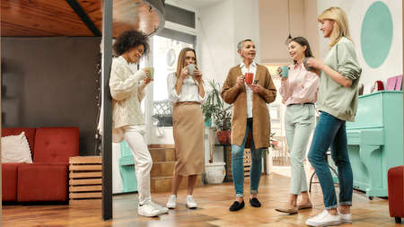 Fashionably dressed women of different age standing together sharing ideas and having hot drinks in a creative workspace 免版税图像 - 157507799