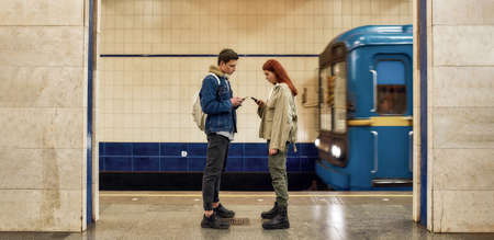 Full length shot of couple of teenagers using smartphones, totally absorbed in online life, ignoring each other while standing at the subway metro station 免版税图像 - 157507804