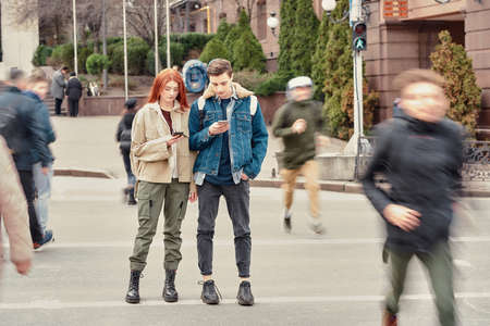 Full length shot of two teenagers totally absorbed in their smartphones, ignoring each other while standing together on the city street 免版税图像 - 157507812