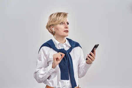 Portrait of elegant middle aged caucasian woman wearing business attire and earphones holding smartphone, looking away while standing isolated over grey background