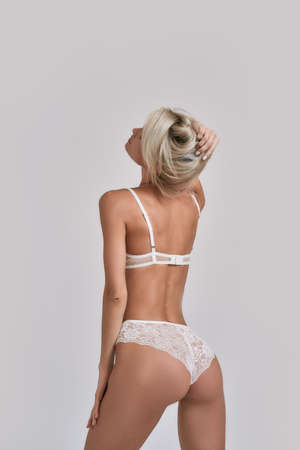 Young sensual woman with perfect body wearing white lingerie looking sexy while posing isolated over grey background