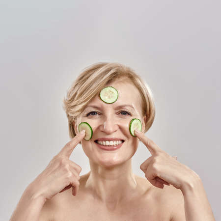 Portrait of attractive middle aged caucasian woman applying cucumber slices on her face as mask, smiling at camera isolated over grey background Stock fotó