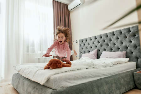 A little barefoot girl enjoying jumping down on her teddybear with her hair back on a bed